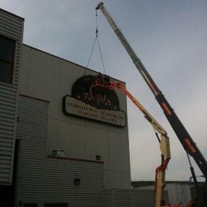 Jeřáb odstraňuje logo Stargate z budovy
